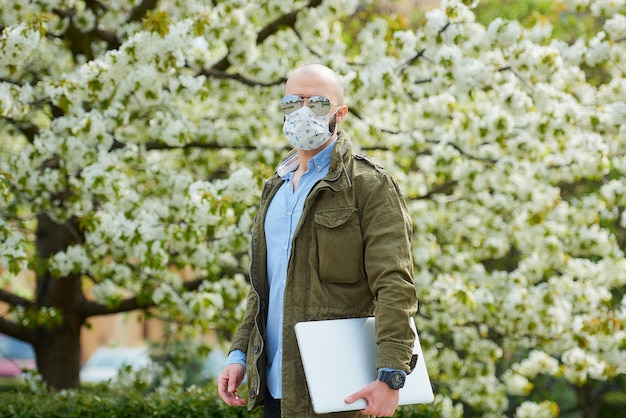 Een kale man met een baard in een medisch gezichtsmasker om de verspreiding van het coronavirus te vermijden, loopt met een laptop in het park. een man draagt een gezichtsmasker n95 en een pilotenzonnebril in de tuin tussen bloeiende bomen.