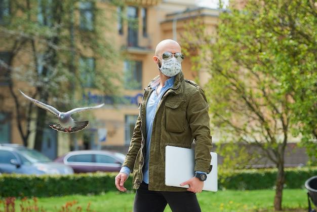 Een kale man met een baard in een medisch gezichtsmasker om de verspreiding van het coronavirus te vermijden, loopt met een laptop in het park. een man draagt een gezichtsmasker n95 en een pilotenzonnebril op straat bij een vliegende duif.