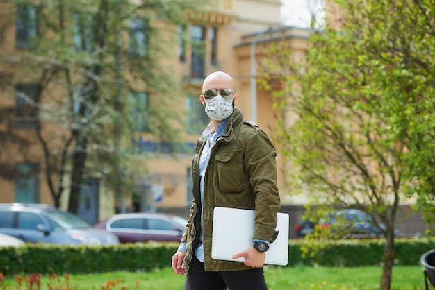 Een kale man met een baard in een medisch gezichtsmasker om de verspreiding van het coronavirus te vermijden, loopt met een laptop in het park. een man draagt een gezichtsmasker n95 en een pilotenzonnebril op straat in de stad.
