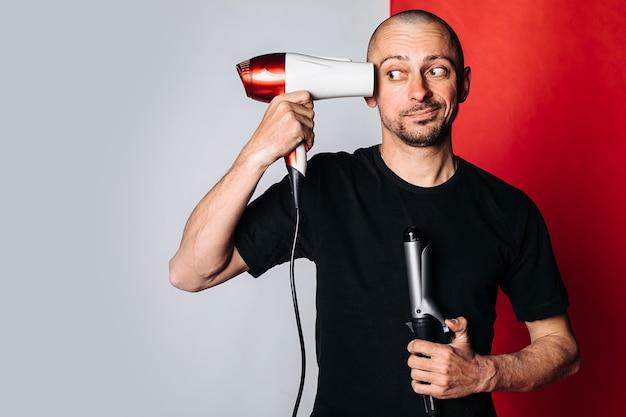 Een kale man, met een föhn en krultang in zijn hand, droogt zijn haar en kaalheid. een man in een zwart t-shirt op een rode en grijze achtergrond. ruimte voor tekst. haarverzorging concept. mannelijke kapper