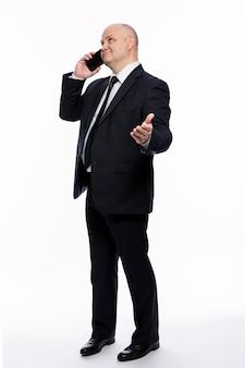 Een kale man van middelbare leeftijd in een strikt zwart pak staat en praat aan de telefoon. zakelijk succes en complexiteit. witte achtergrond. verticaal.