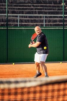 Een kale man van middelbare leeftijd speelt emotioneel tennis op het veld. buitenshuis