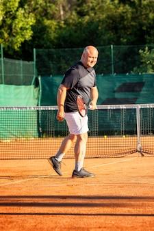 Een kale man van middelbare leeftijd speelt emotioneel tennis op het veld. verliest de tegenstander. buitenshuis