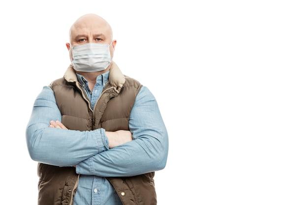 Een kale volwassen man in een medisch masker staat met zijn armen over elkaar op zijn borst. voorzorgsmaatregelen in quarantaine geplaatst voor de periode van de coronviruspandemie. geïsoleerd op een witte muur. ruimte voor tekst.
