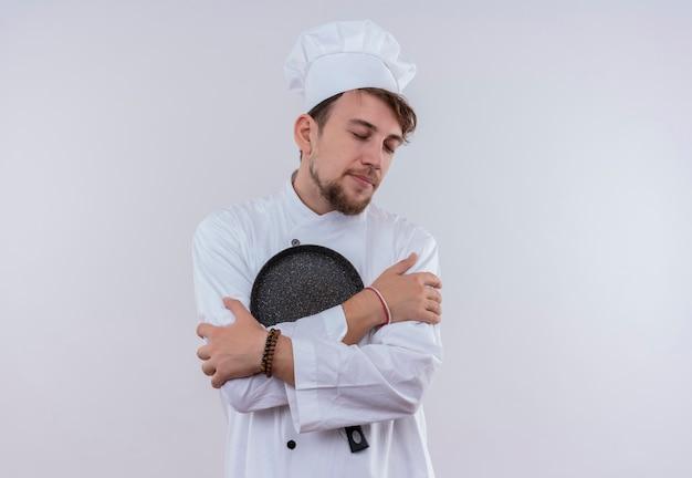 Een kalme jonge bebaarde chef-kok man in wit uniform knuffelen koekenpan met gesloten ogen op een witte muur