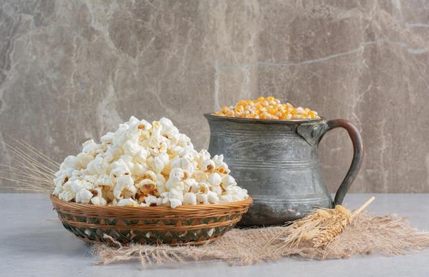 Een kan met maïskorrels en een enkele tarwesteel naast een geweven mand met popcorn op een stuk stof op een marmeren oppervlak