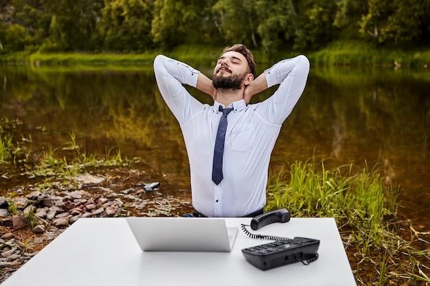 Een kantoormedewerker drinkt spieren terwijl hij in een kantoor aan tafel zit met een laptop en een vaste telefoon met drukknop.
