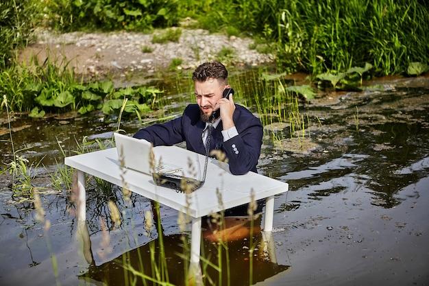 Een kantoormedewerker, een bediende of een zakenman gekleed in een pak, zit aan een wit bureau, praat op de vaste telefoon en drukt op de toetsen van de laptop, het zakenkantoor bevindt zich in de rivier.