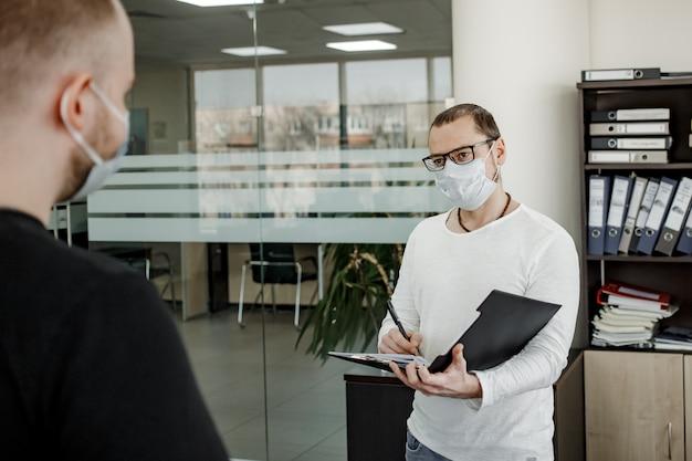 Een kantoormedewerker in een beschermend masker praat met een klant