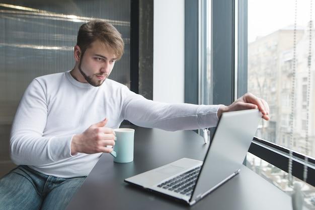 Een kantoormedewerker met een kop warme drank in zijn handen begint te werken op een laptop.