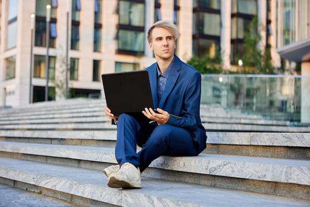 Een kantoormedewerker met een laptop op zijn knieën zit op de trede voor het gebouw van het zakencentrum