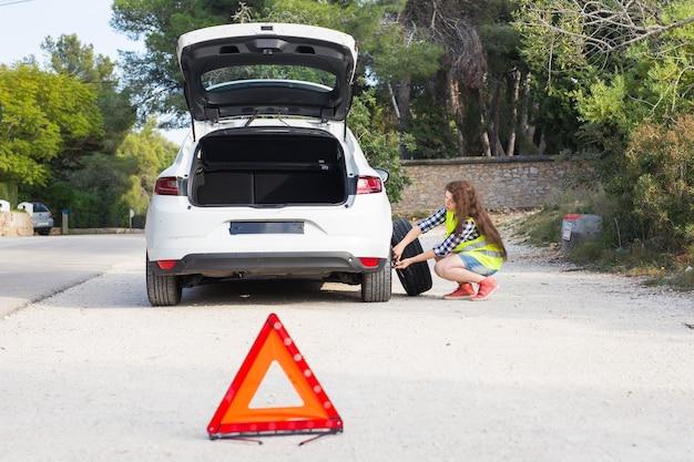 Een kapotte auto, een teken van een ongeval en een vrouw begrijpt wat er aan de hand is