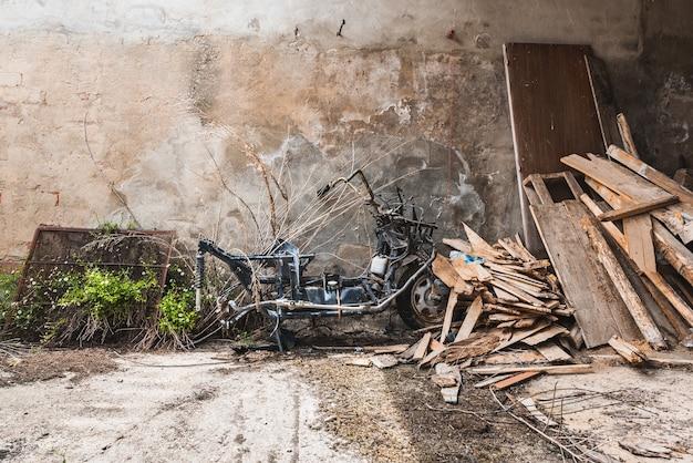 Een kapotte oude motorfiets tussen houten puin Premium Foto