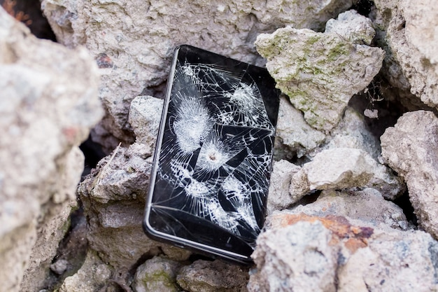 Een kapotte telefoon met een gat uit de kogel zit tussen de stenen