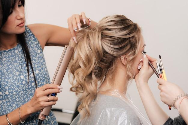 Een kapper en een visagist doen samen hun haar en make-up in een professionele salon
