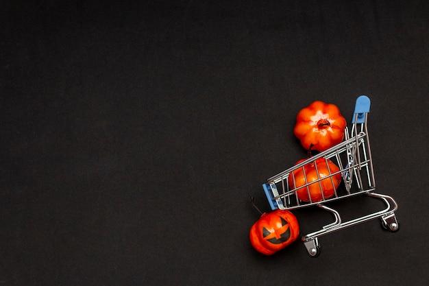 Een kar met oranje pompoenen op een zwarte achtergrond. ronduit over het onderwerp verkoop in halloween. kopieer ruimte