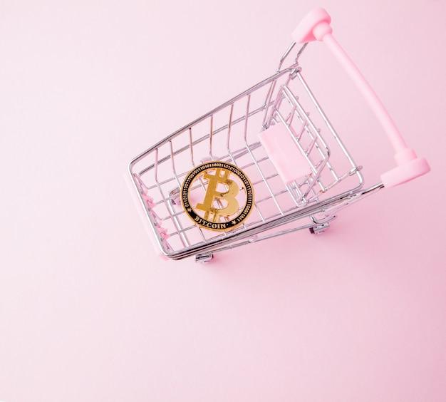 Een kar van een supermarkt, bitcoin op een houten achtergrond. internet, cryptovaluta.