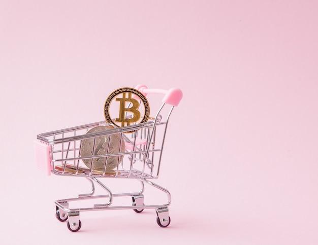 Een kar van een supermarkt, bitcoin op een houten achtergrond