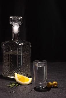 Een karaf en een klein glas wodka of andere kleurloze alcoholische drank op een zwarte achtergrond