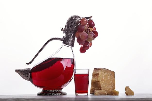 Een karaf rode wijn, een glas wijn, dure kazen, kaas met schimmel, zwarte kaas en druiven. op witte achtergrond. plaats voor logo.