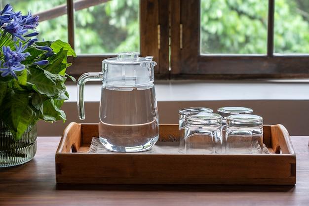 Een karaf water en vier lege glazen op een houten dienblad naast het raam