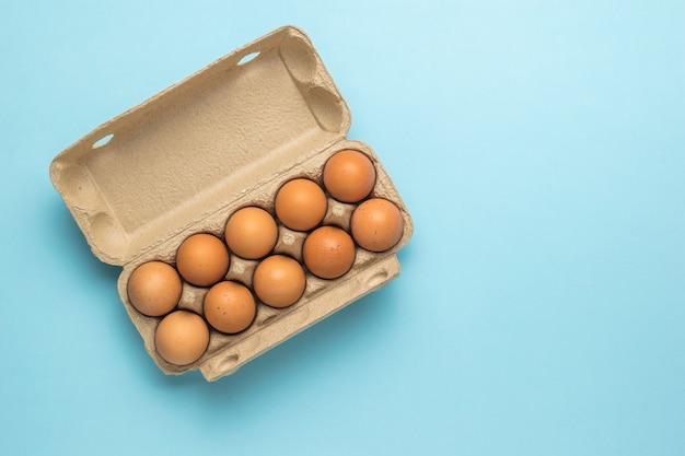Een kartonnen doos met tien eieren op een blauwe achtergrond. een natuurproduct.
