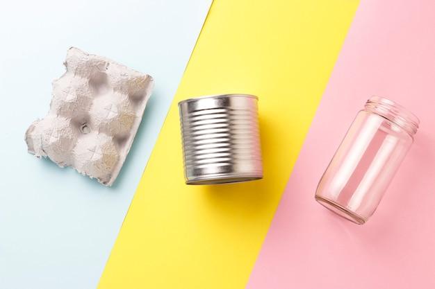 Een kartonnen en glazen pot, ijzer afval op gele en roze achtergrond, bovenaanzicht.