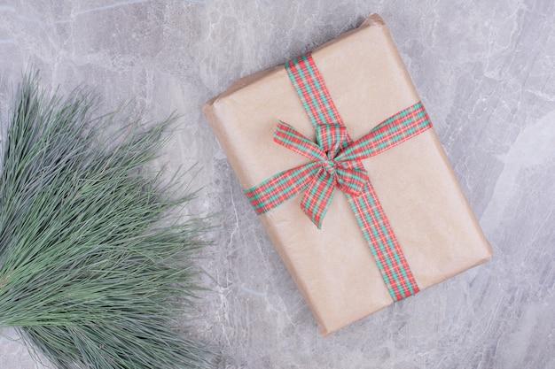 Een kartonnen geschenkdoos met kerstlint erop.