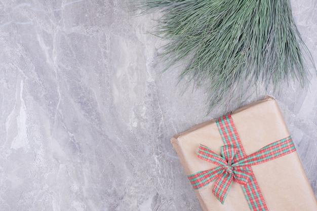 Een kartonnen geschenkdoos omwikkeld met lint en kruiden