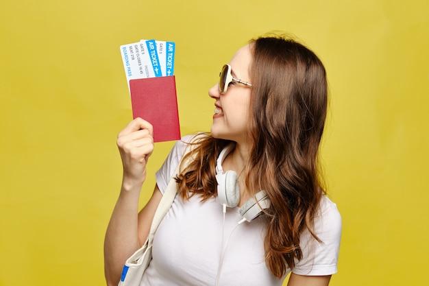 Een kaukasisch meisje in glazen bekijkt een paspoort met vliegtickets op een gele achtergrond als vakantieconcept.