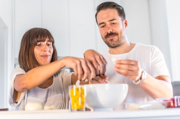 Een kaukasisch paar dat samen thuis kookt, in beslotenheid kookt, met het gezin kookt.