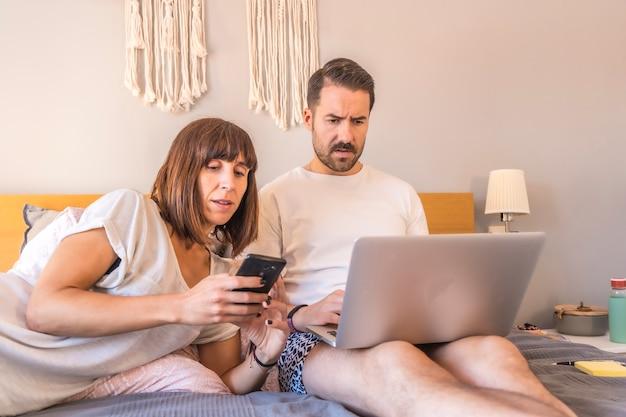 Een kaukasisch paar op het bed met een computer en een telefoon, het maken van een reservering in een hotel of vlucht, het organiseren van vakanties, nieuwe technologieën in familie. als koppel naar de beste deals kijken