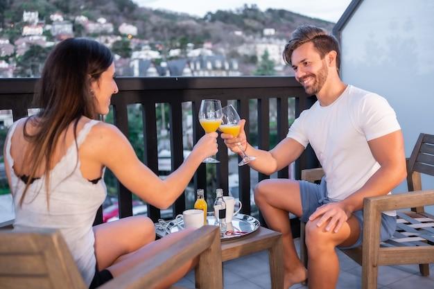 Een kaukasisch stel ontbijten op het hotelterras in pyjama's. een sinaasappelsap in de ochtend, levensstijl van een verliefd stel