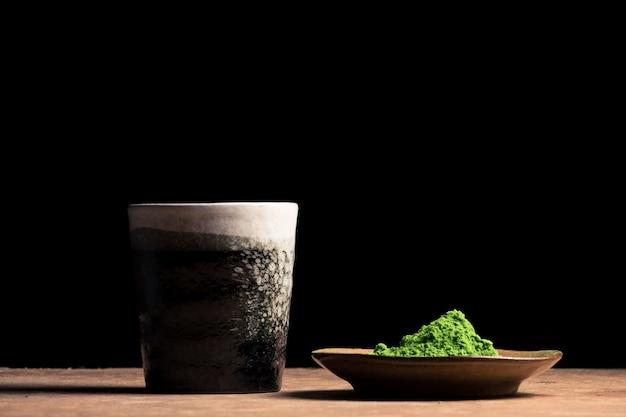 Een keramische kop en groene thee poeder op de tafel