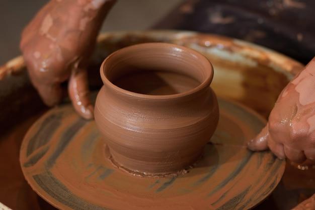 Een keramist beeldhouwt een aarden pot op een pottenbakkersschijf een draaiende pottenbakkersschijf en keramiek erop