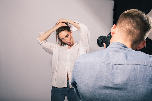 Een kerelfotograaf maakt foto's van een meisjesmodel in een studio op wit