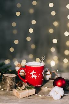 Een kerst rode kopje koffie op een verlichting oppervlak