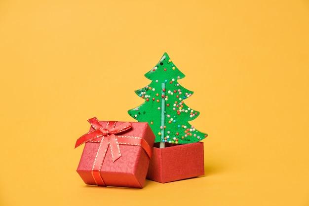 Een kerstboom groeit uit een open geschenkdoos. kerstboom gevormde lollydoos op gele achtergrond met exemplaarruimte.