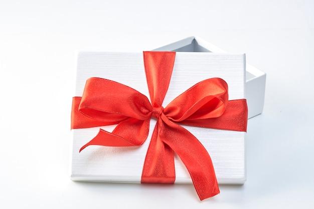 Een kerstcadeau in wit inpakpapier en rode linten