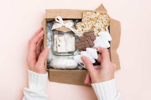Een kerstcadeau. vrouwenhanden zijn in een doos gevouwen, een pot met pasta, ontbijtgranenchips en gebreide sparren. handwerk decor. zero waste