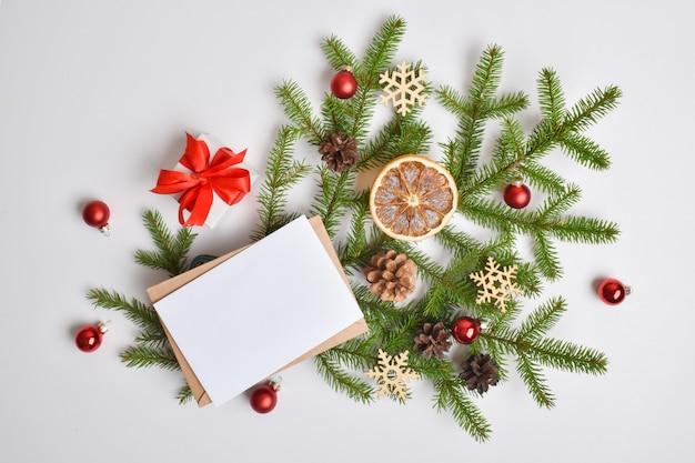 Een kerstkaart met een envelop en een tak van een dennenboom, sinaasappels en kerstspeelgoed op een witte achtergrond. f