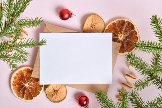 Een kerstkaart met een envelop en een tak van een dennenboom, sinaasappels en kerstspeelgoed.