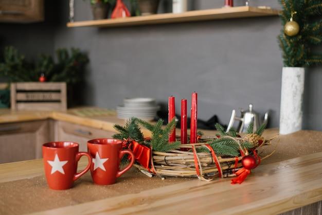 Een kerstkrans met rode kaarsen op de houten tafel en twee rode mokken in de keuken,