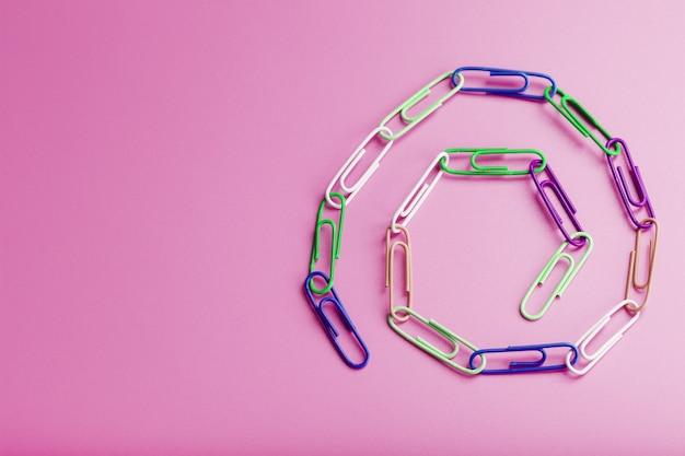 Een ketting van veelkleurige paperclips op een roze achtergrond. bedrijfscommunicatie en samenwerkingsconcept