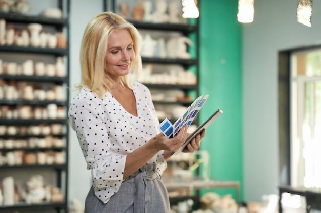 Een keuze maken creatieve volwassen zakenvrouw ondernemer met behulp van tablet pc kleurstalen kiezen