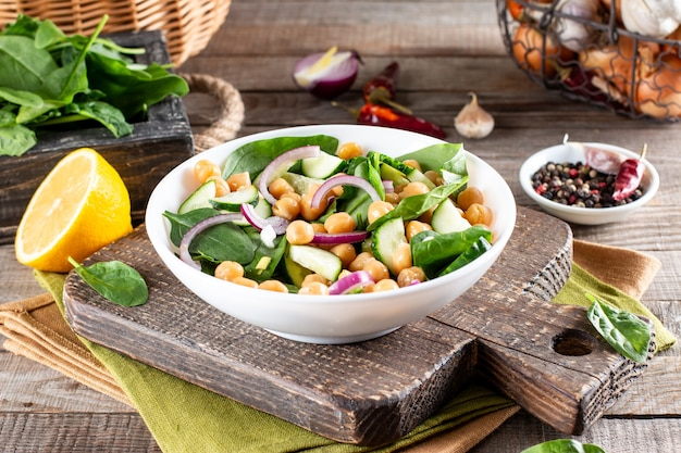 Een kikkererwten (garbanzo bean) salade op een plaat op een houten tafel