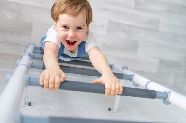 Een kind aan de zweedse muur sport thuis, een jongen klimt met een touw op een ladder, het concept van sport en gezondheid