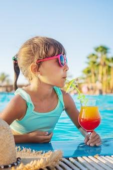 Een kind aan zee drinkt een cocktail. selectieve aandacht. kind.