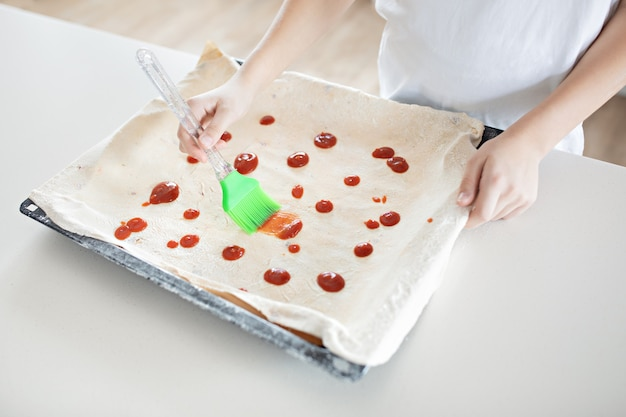 Een kind bereidt italiaanse pizza thuis keuken. het kind smeert het deeg met ketchup. kinder concept chef. lifestyle, openhartig moment
