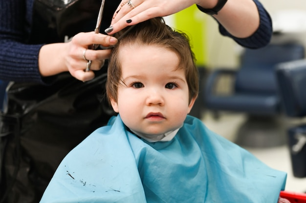 Een kind bij de kapper. het eerste kapsel van het kind bij de kapper. baby kapsel peuter.